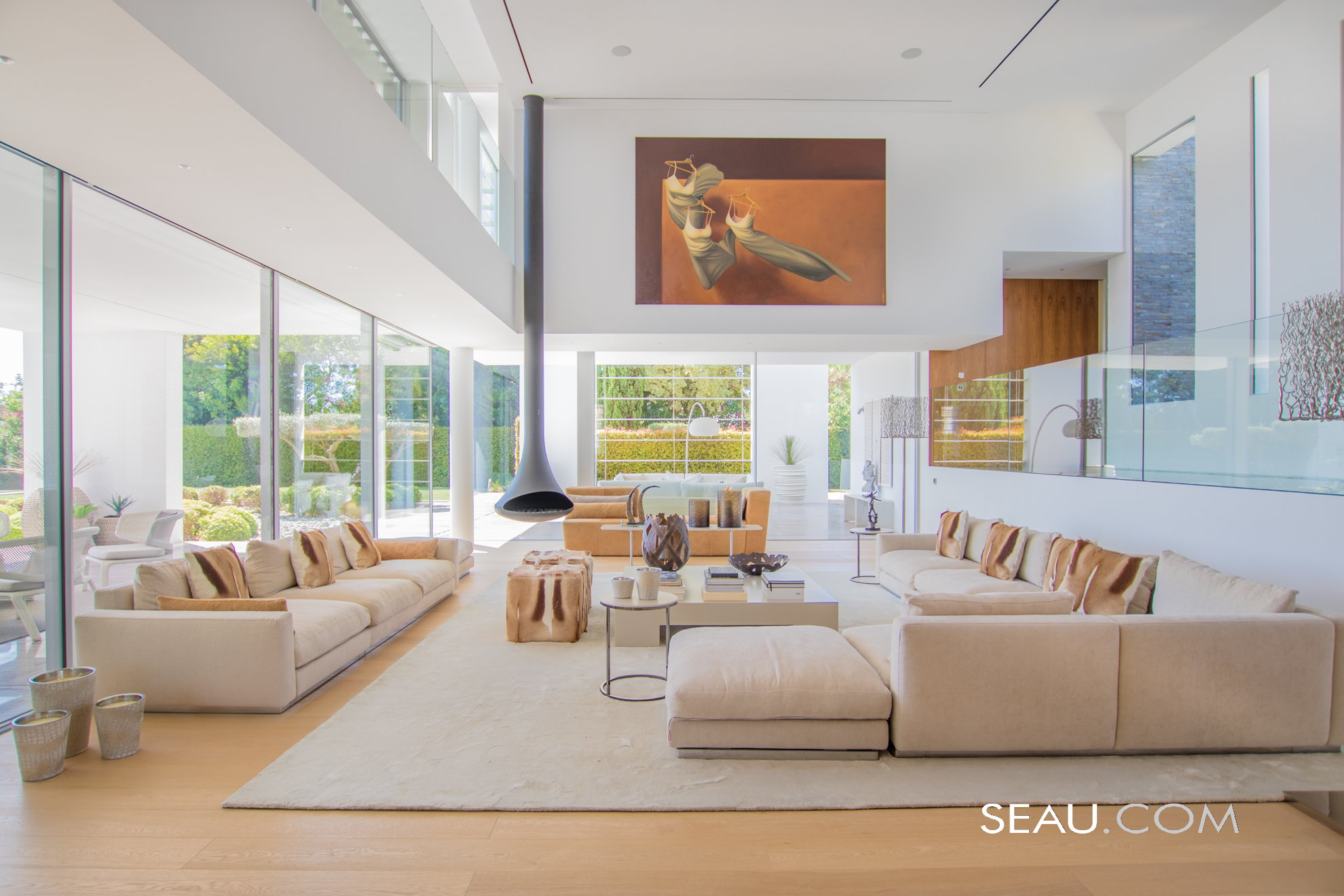 The main living room with double height ceiling, has plenty of space to entertain, and a cozy contemporary feeling reinforced by a metal suspended fireplace. .